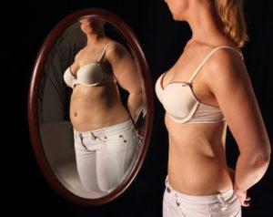 ragazza che si guarda allo speccio e soffre di anoressia
