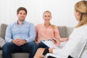 Happy Young Couple Sitting On Sofa Consulting With Psychologist